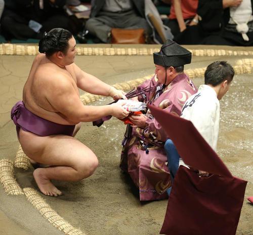 鶴竜を破り、座布団が舞う中懸賞金の束を手にする朝乃山(撮影・河田真司)