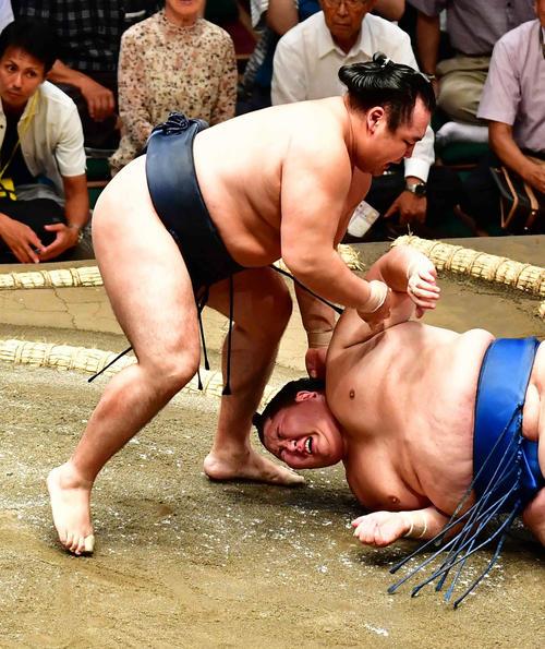 11日、鶴竜(左)に肩すかしで敗れた逸ノ城は右肩を痛め苦悶(くもん)の表情を見せる(撮影・小沢裕)