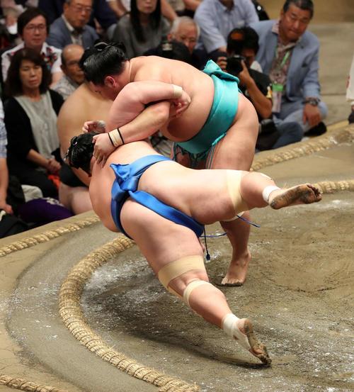 琴奨菊(手前)をすくい投げで破る明生(撮影・鈴木正人)