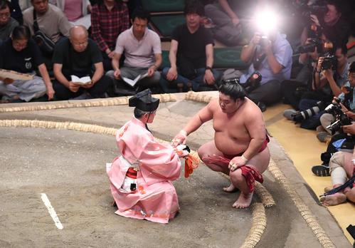 大栄翔(右)は押し出しで明生を下し、懸賞金を受け取る(撮影・加藤諒)