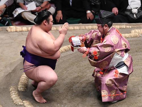 貴景勝(左)は押し出しで竜電を下し、懸賞金の束を受け取る(撮影・加藤諒)
