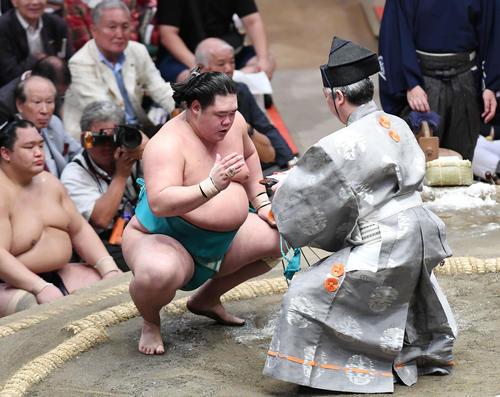明生(左)は寄り切りで朝乃山を下し、懸賞金を受け取る(撮影・加藤諒)