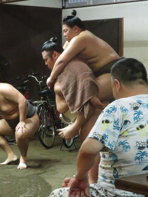 台風に備えて力士の自転車が運び込まれた稽古場で、若い衆を背負ってスクワットする貴景勝。手前は千賀ノ浦親方