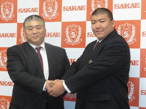 大嶽部屋への入門を発表し、大嶽親方(左)と握手を交わす納谷幸成