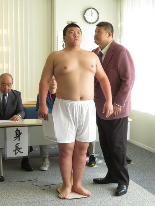 新弟子検査で身長を測定する納谷幸成(中央)。右は錦戸親方、左は花籠親方(撮影・高田文太)