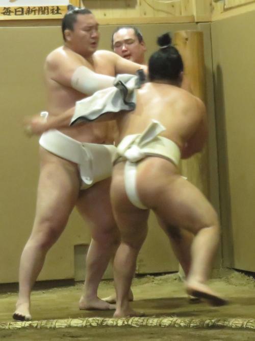 三番稽古で熱が入るあまり突っかける石浦(背中)と幕下力士の仲裁に入る白鵬(左)