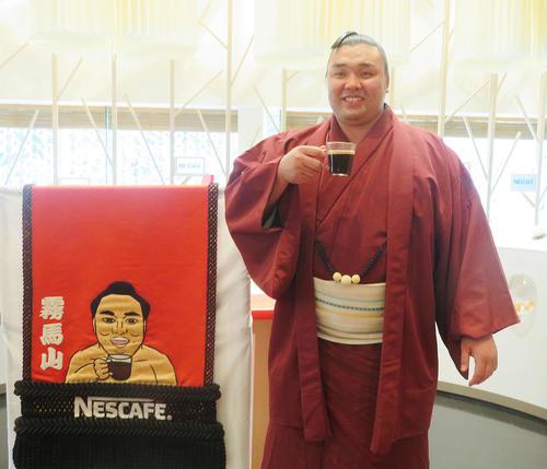 ネスレ日本から化粧まわしを贈呈され、化粧まわしのデザインと同じくコーヒーを飲む霧馬山(撮影・佐藤礼征)