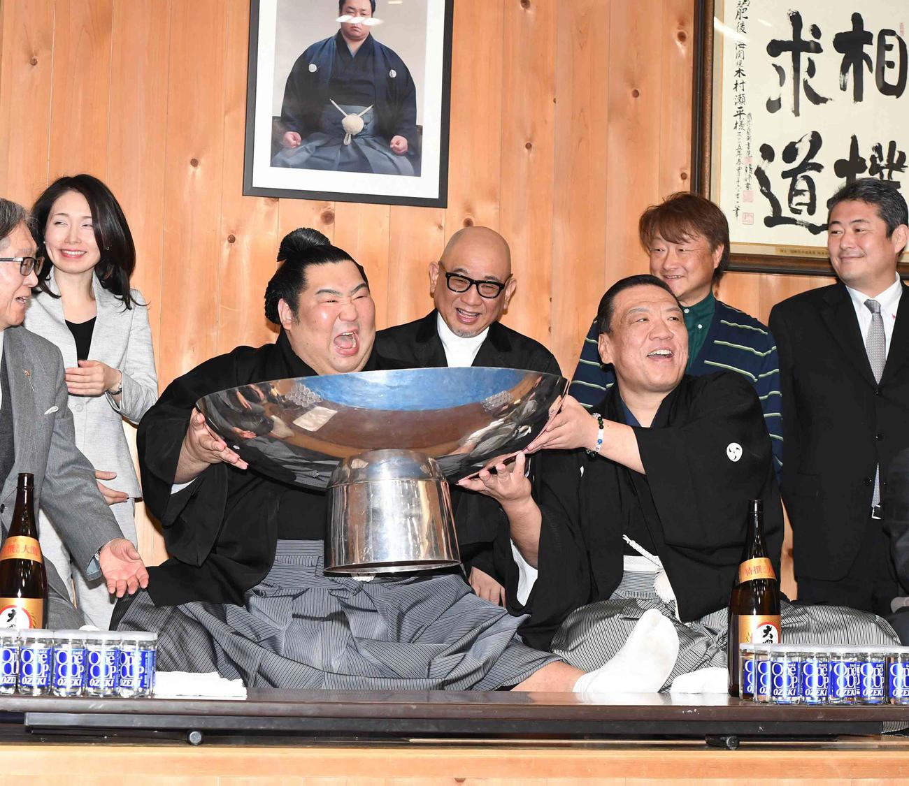 初優勝を飾り部屋に戻った徳勝龍は、木瀬親方(右)の力を借りながら大盃につがれたお酒を飲み、おどけた表情を見せる(撮影・小沢裕)