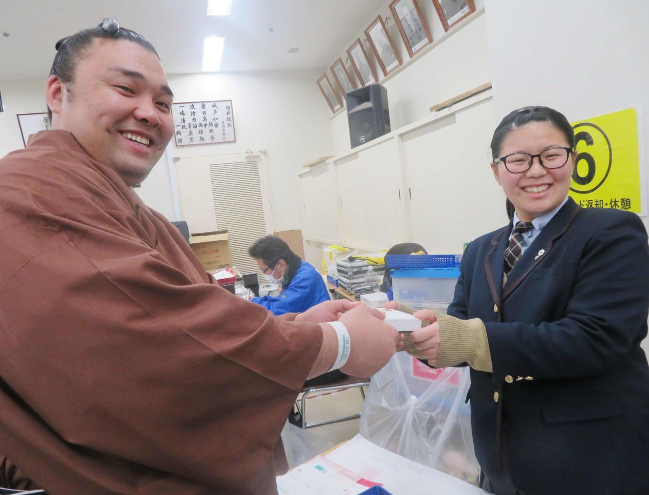 献血に参加し、日本相撲協会が用意したチョコレートをボランティアの女子高生から手渡される霧馬山