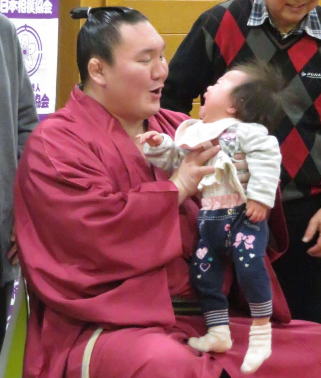 赤ちゃん抱っこ撮影会で、泣き出した子どもをあやす白鵬=2019年2月26日