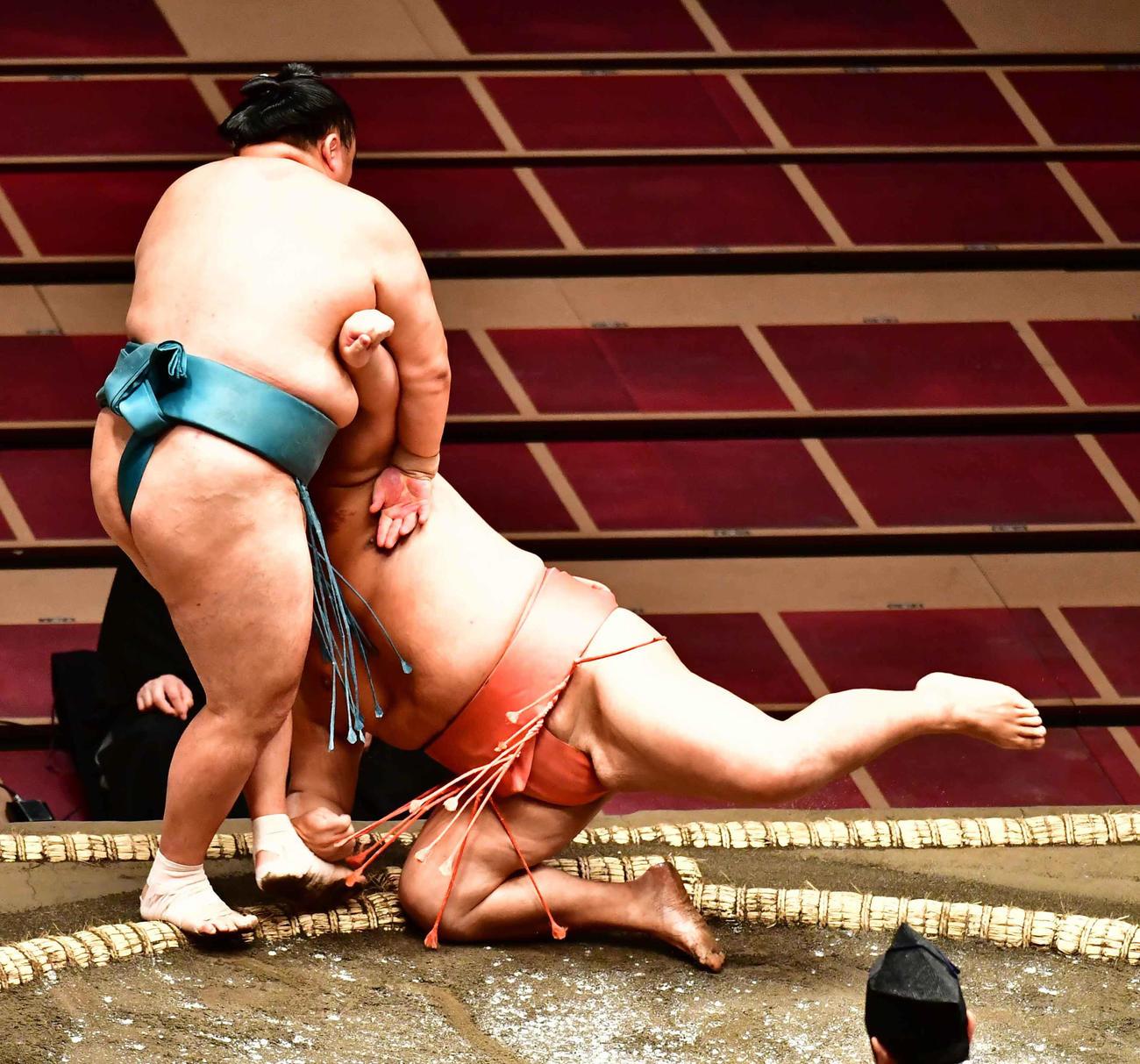 玉鷲(左)は小手投げで千代大龍を下す(撮影・小沢裕)