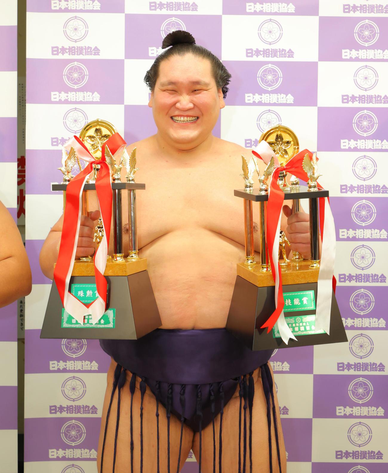 三賞の記念撮影で殊勲賞と技能賞のトロフィーを手に笑顔を見せる照ノ富士(代表撮影)