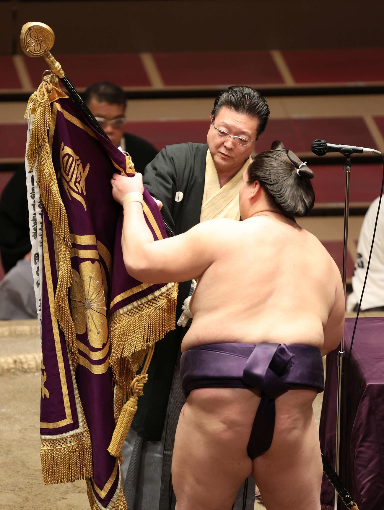 引退を引き留めた師匠の伊勢ケ浜親方から優勝旗を受けとる照ノ富士(2020年8月1日)