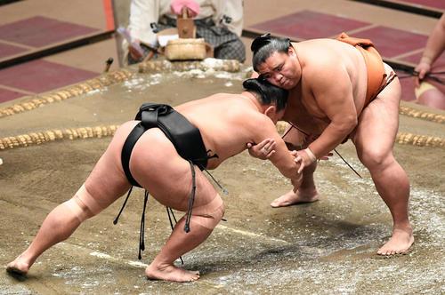 照強(左)の腕を取る御嶽海(撮影・滝沢徹郎)