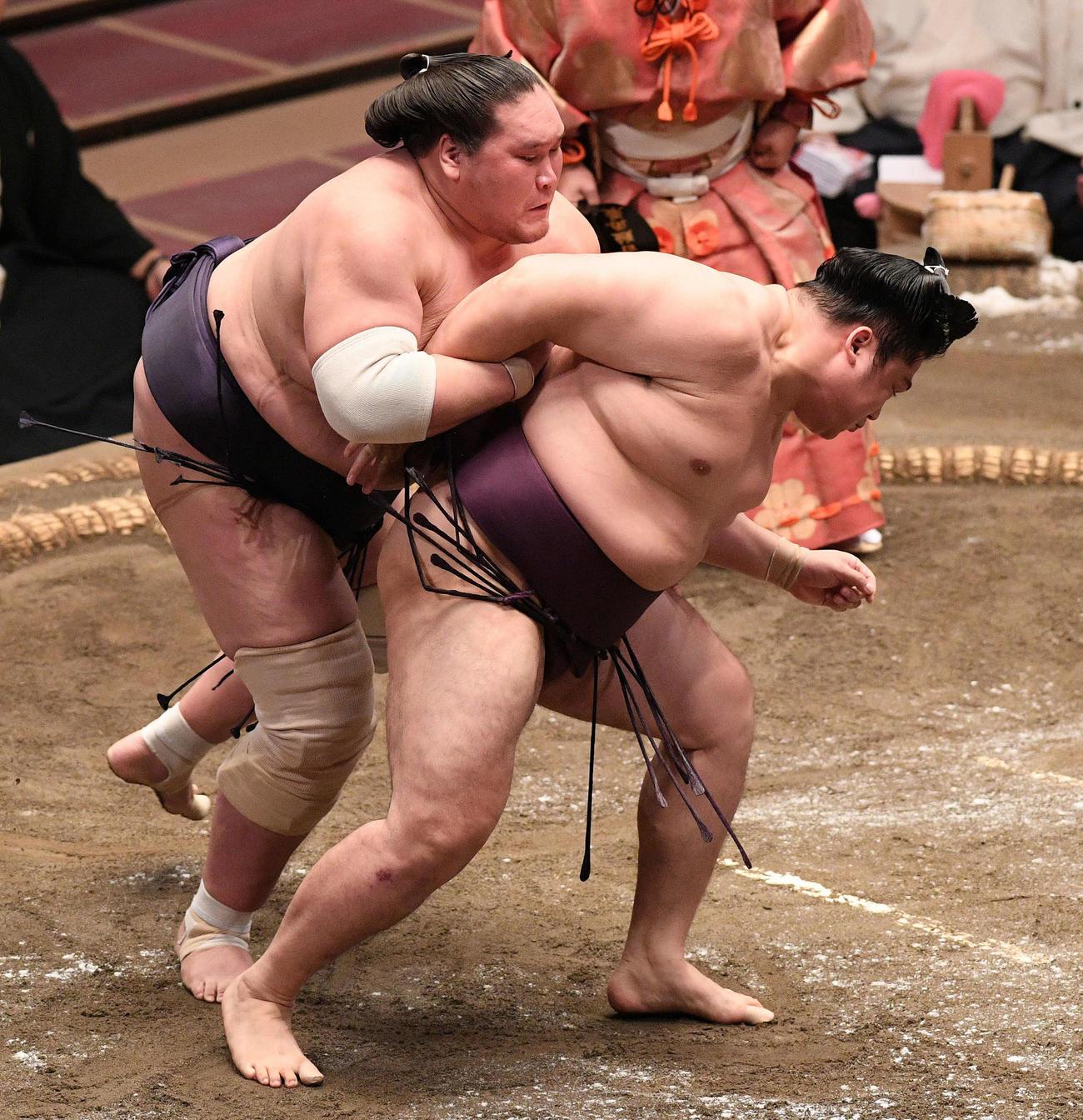 遠藤(右)を送り出しで破る照ノ富士(撮影・滝沢徹郎)