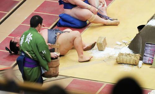 琴恵光に押し出され、まき塩と一緒に土俵下に落ちる徳勝龍(撮影・河田真司)