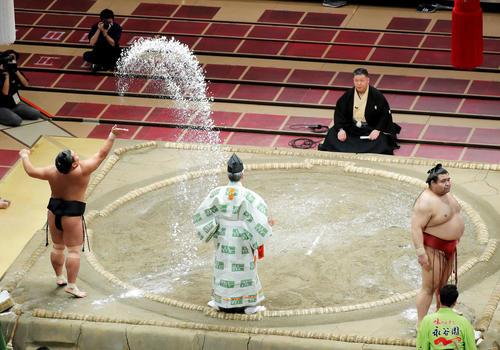 豪快に塩をまく照強(左)と、観客席を見つめる高安(撮影・河田真司)