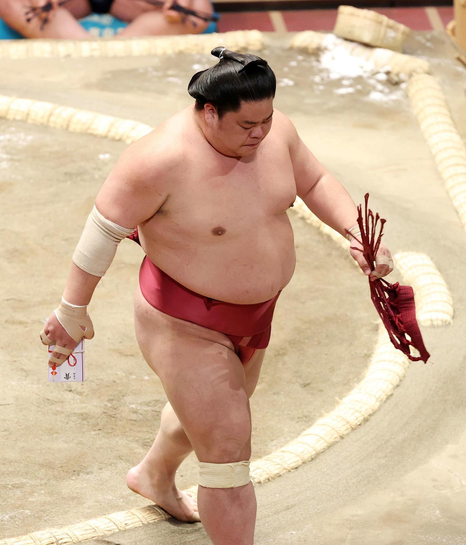 懸賞金の束を手に土俵を引き揚げる大栄翔(撮影・鈴木正人)