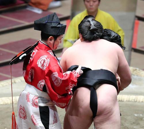 霧馬山(右)のまわしが外れ、締め直す行司の式守勘太夫(撮影・河田真司)