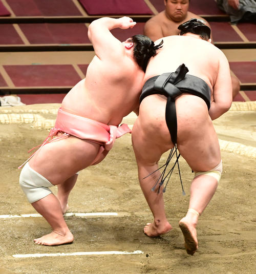 宇良(左)は居反り狙いのような体勢で東龍の下に潜り込む(撮影・小沢裕)