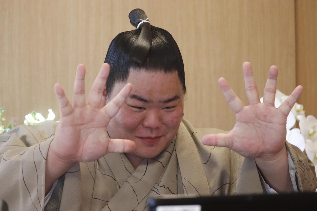 初優勝した初場所から一夜明け、リモートでの会見に出席して自慢の大きな手を画面越しの報道陣に見せる大栄翔(日本相撲協会提供)