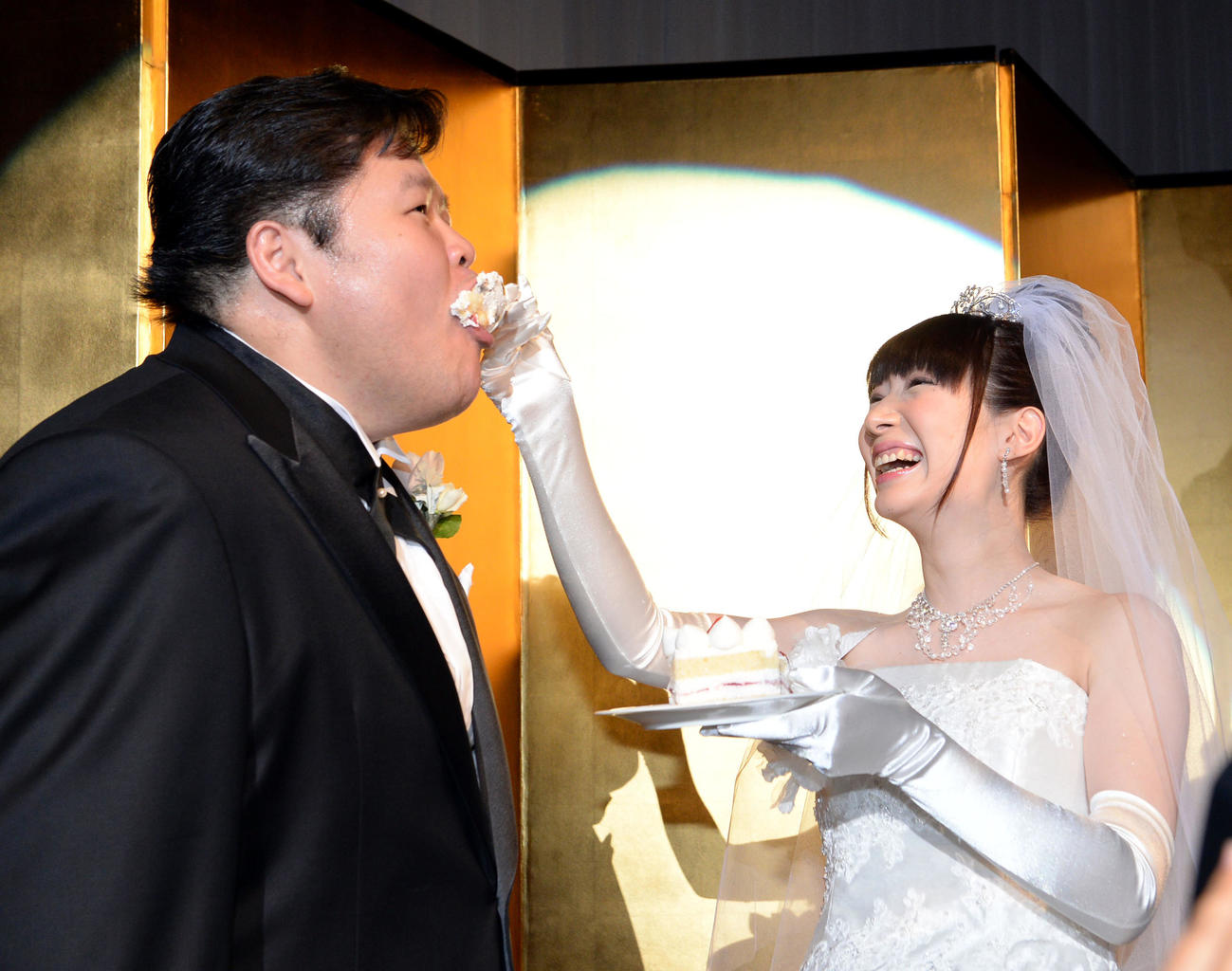 結婚披露宴でケーキを食べさせ合う時津風親方(当時は安治川親方)とアイドルマジシャンの小泉エリ(16年10月2日)