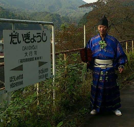 大行司駅のホームにて、装束でポーズを取る木村銀治郎