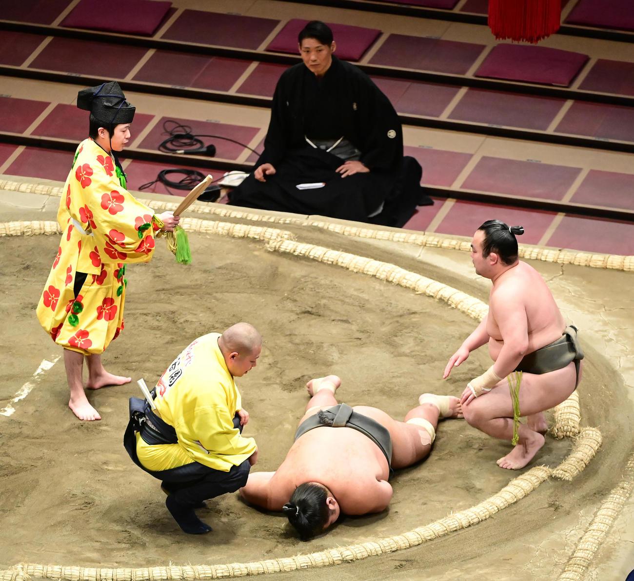 響龍(中央)は土俵にうつぶせのまま動くことができず。右は勝ち名乗りを受ける今福(撮影・小沢裕)