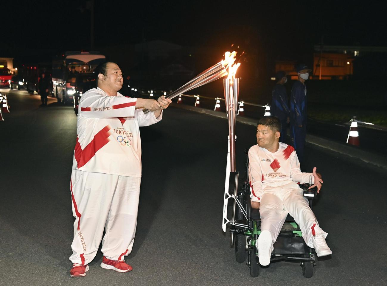 中平誠さん(右)から聖火を引き継ぐ大相撲の井筒親方=19日午後、高知県宿毛市(代表撮影)