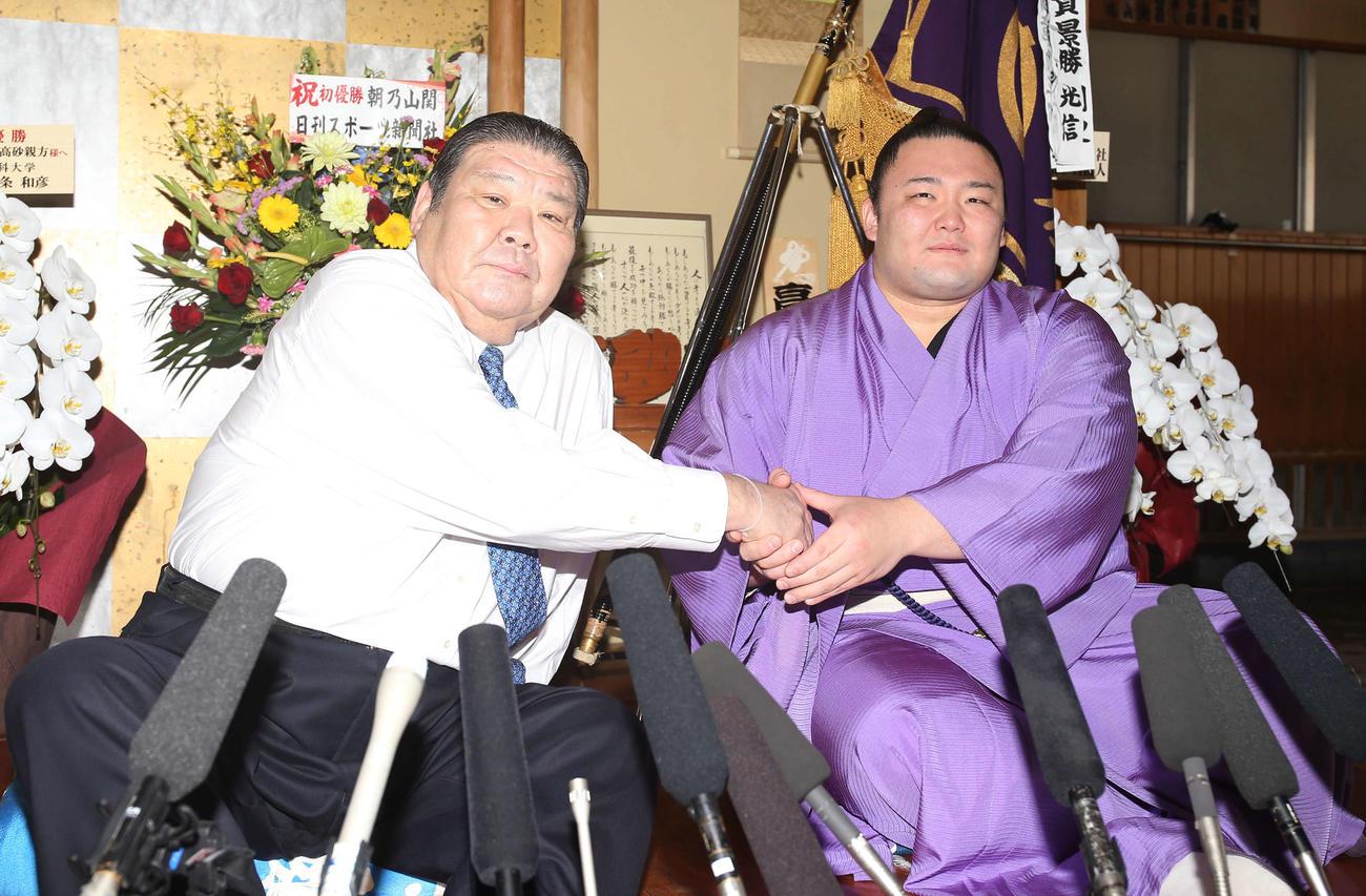 元朝潮の錦島親方(左)と握手を交わす朝乃山(2019年5月27日撮影)