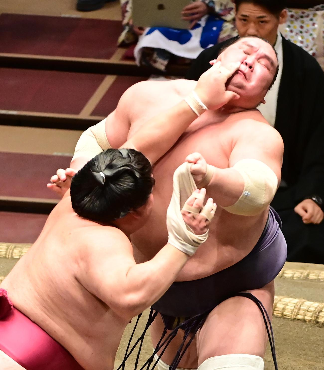 照ノ富士(右)を突き押しで攻める大栄翔。照ノ富士の左手が絡まり大栄翔の右手に巻いていたサポータが外れて宙を舞った(撮影・小沢裕)