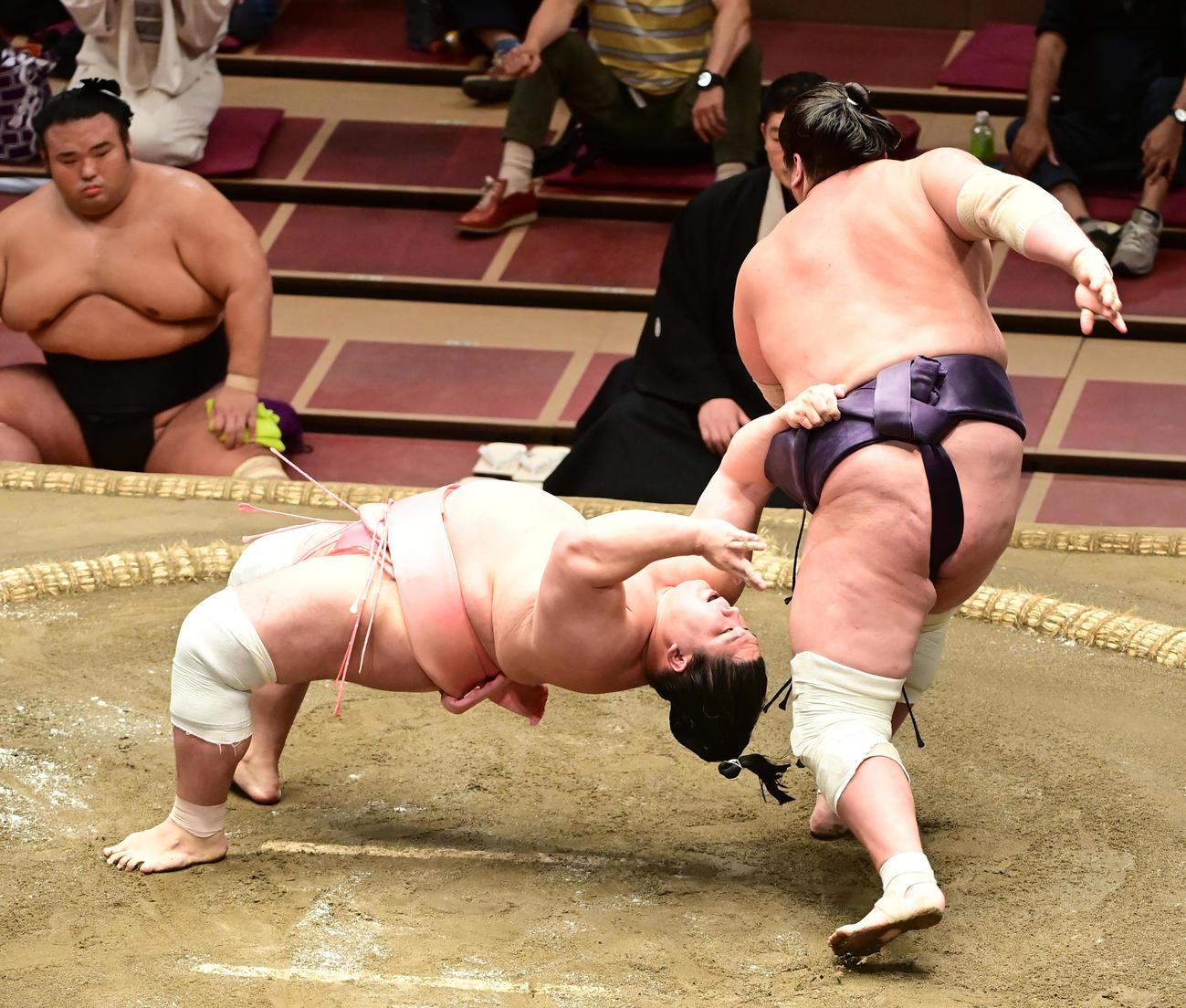 照ノ富士(右)の上手投げをまわしをつかんで必死にこらえる宇良(撮影・小沢裕)