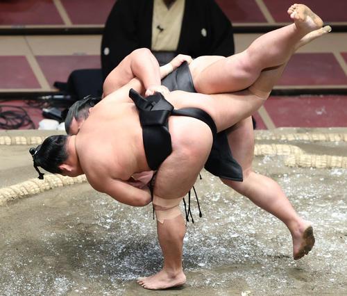 千代ノ皇(奥)を掛け投げで破る照強(撮影・河田真司)