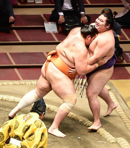 魁聖(左)は寄り切りで大奄美を破る(撮影・小沢裕)