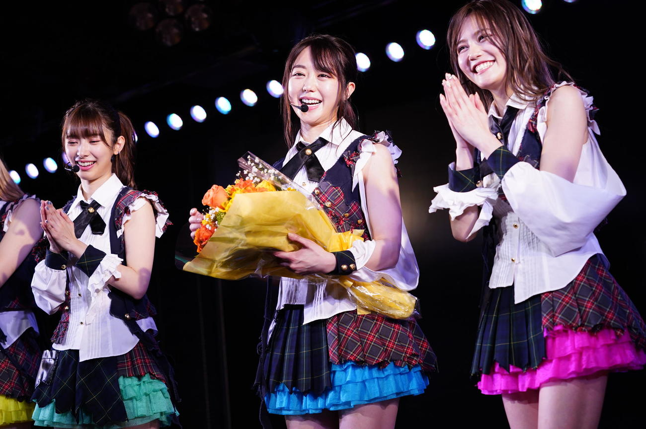 劇場出演1000回を達成し花束を手に笑顔の峯岸みなみ(中央)。左は武藤十夢、右は込山榛香(C)AKS