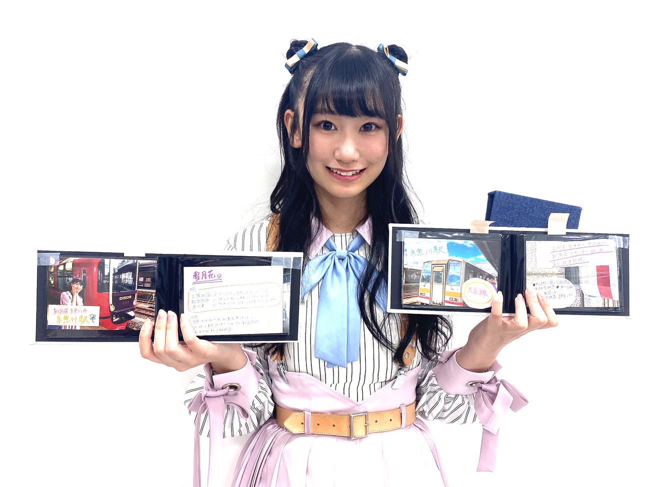 大好きだという鉄道との写真を納めたアルバムを手に笑顔を見せる佐藤海里(C)Flora