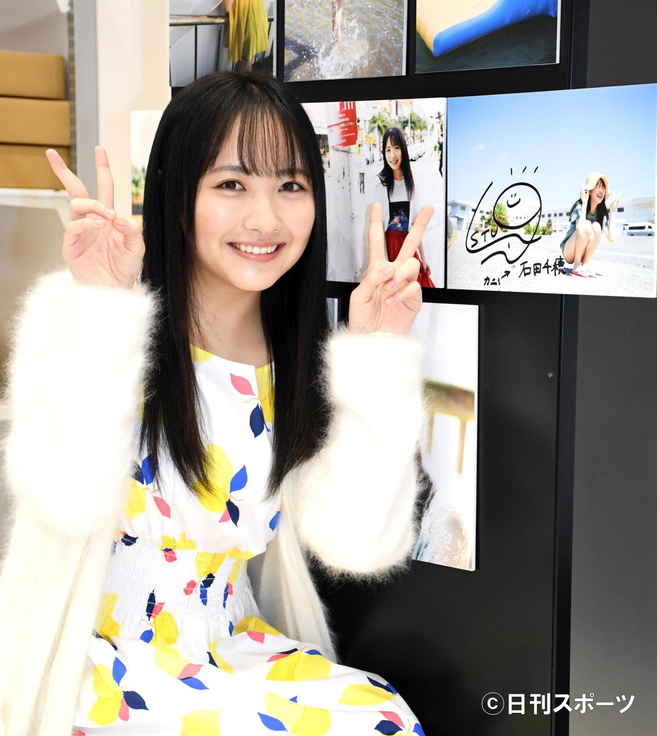 初の写真集「檸檬の季節」発売イベントで展示されるパネルにサインして笑顔のSTU48石田千穂(撮影・大友陽平)