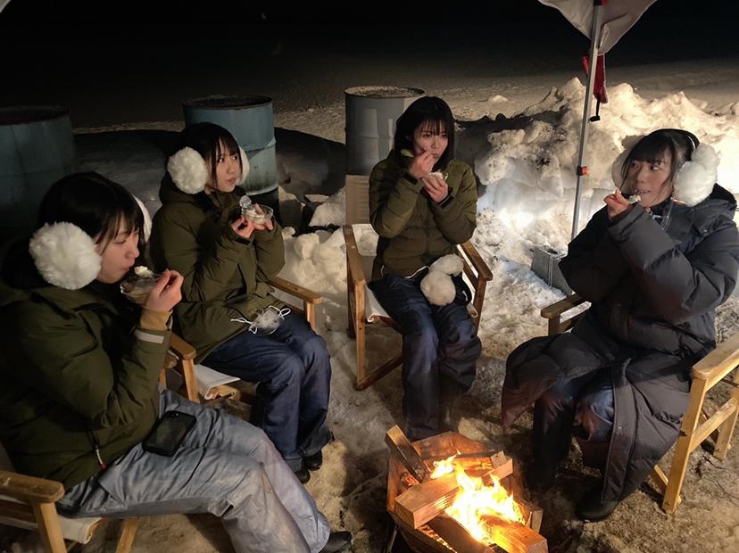 たき火を囲む、左から佐藤海里、對馬優菜子、安藤千伽奈、藤崎未夢(c)Flora