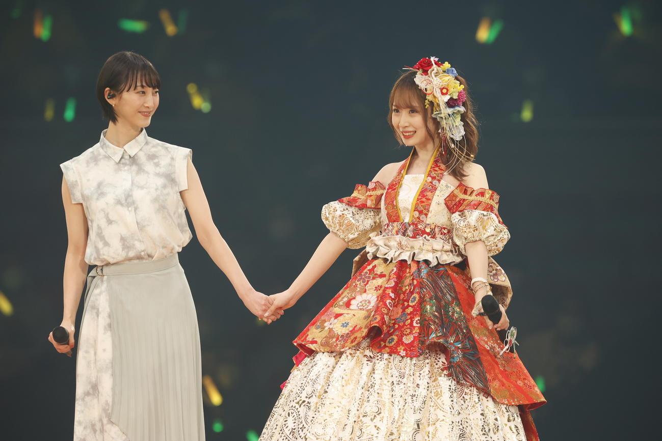 卒業コンサートにサプライズで登場した松井玲奈(左)と手をつなぐ高柳明音(c)2021 Zest,Inc./AEI