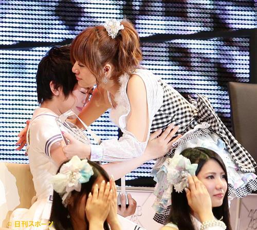 第5回AKB48選抜総選挙開票イベント 8位になった高橋みなみ(右)は席に着く前、峯岸みなみと抱擁を交わす=13年6月