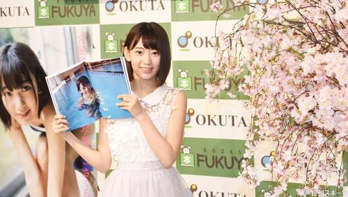 初写真集「さくら」の発売記念イベントを行ったHKT48の宮脇咲良は、お気に入りのページを開きながら桜の横で笑顔を見せる(2015年7月撮影)