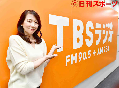 TBSラジオの看板の前でポーズをとる堀井美香アナウンサー(撮影・小沢裕)