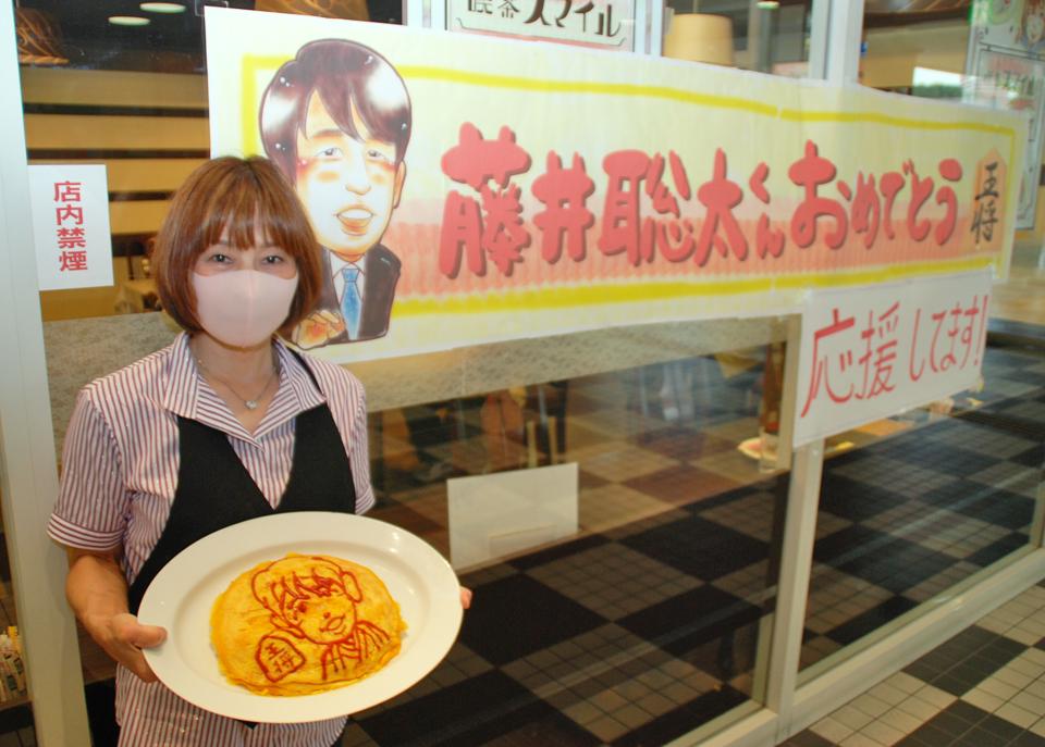 藤井聡太七段の似顔絵ポスターの横で特大オムライスを持つ「喫茶スマイル」の店主、鈴木松子さん(撮影・松浦隆司)