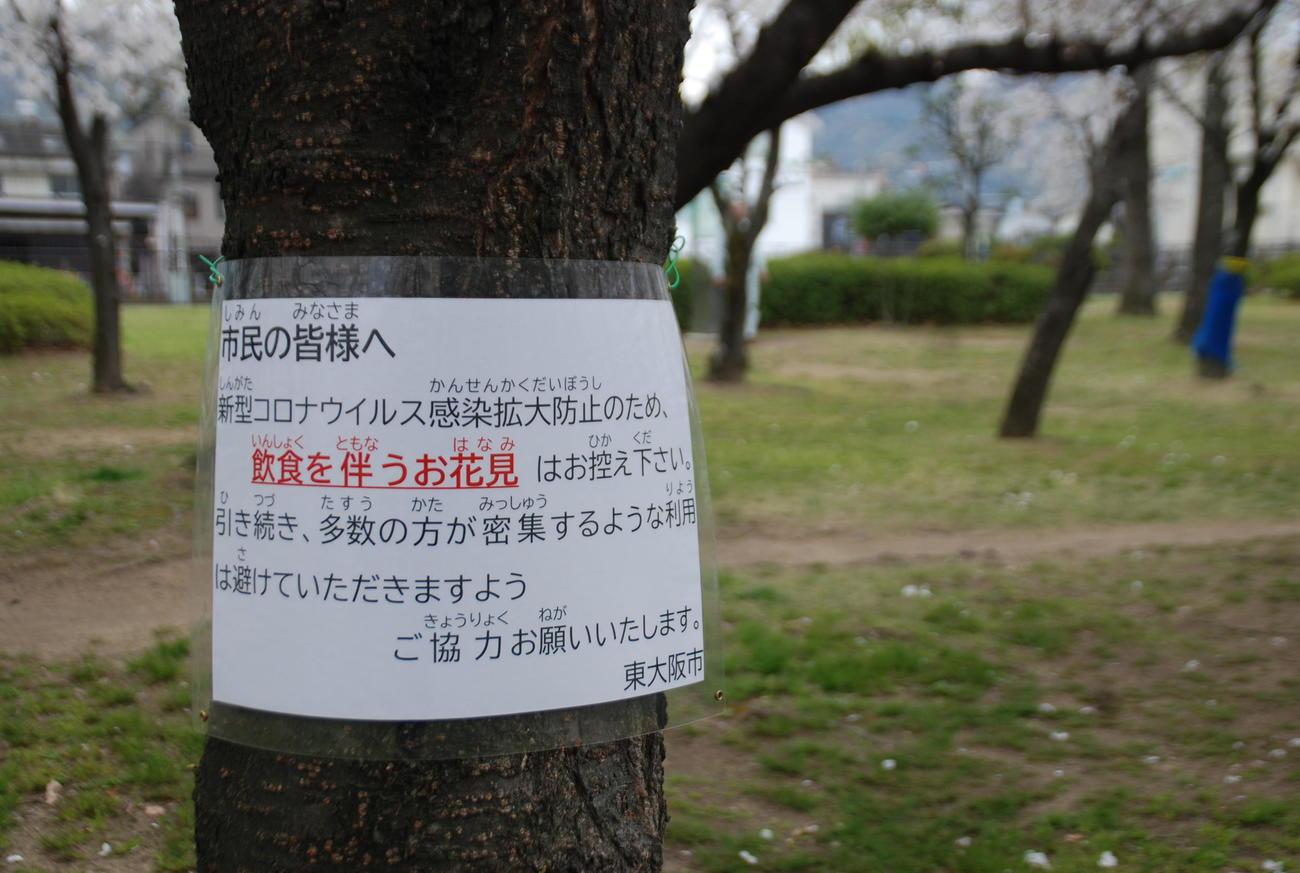 今春の花見シーズン、東大阪市の花園中央公園の桜の木には「飲食を伴う花見はお控え下さい」の貼り紙(撮影・松浦隆司)