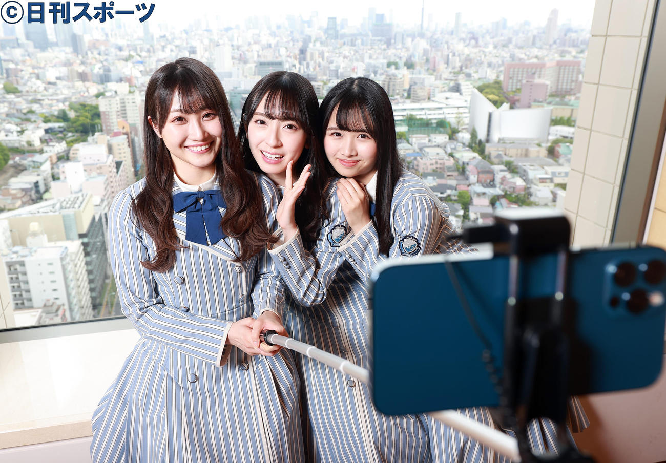 自撮り棒で笑顔で写る日向坂46の、左から潮紗理菜、金村美玖、上村ひなの(撮影・浅見桂子)
