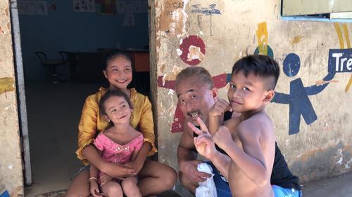 カンボジアで現地の子どもたちと触れ合う角田信朗(右から2人目)