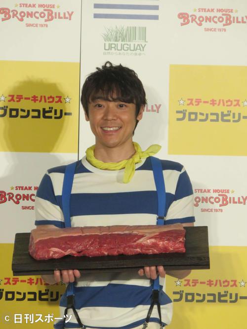 ウルグアイ牛のステーキ肉の塊を持つ小林よしひさ