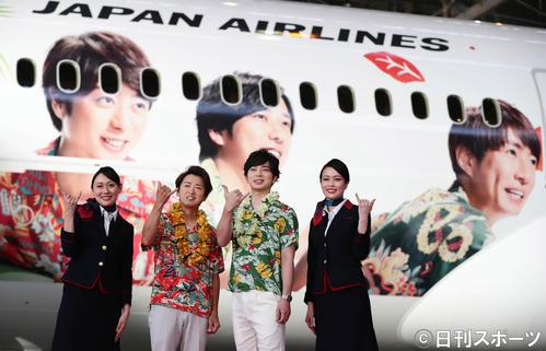 メンバーが描かれたJAL特別塗装機の前で客室乗務員と写真に納まる嵐の大野智(左)と松本潤(撮影・丹羽敏通)