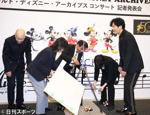 フォトセッション時にセッティングしたミッキーのぬいぐるみを、またもスタッフが崩してしまい思わず爆笑してしまう稲垣吾郎(右)と音楽監督の島健(左)(撮影・河田真司)