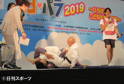 「兵庫県オールトヨタスポーツフェスティバル」で、パラ柔道の広瀬誠氏(中央右)と対戦するサバンナ八木(中央左)。左はMCの陣内智則(撮影・星名希実)